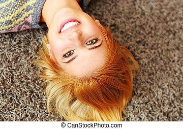 mulher, jovem, closeup, lar retrato, sorrindo, mentindo, tapete