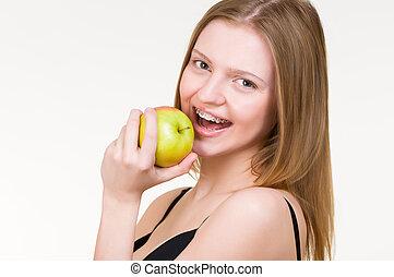 mulher jovem, com, suportes, comendo maçã