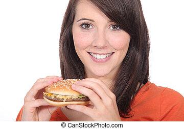 mulher jovem, comer, hambúrguer