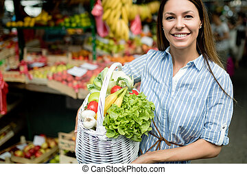 mulher jovem, comprando, legumes
