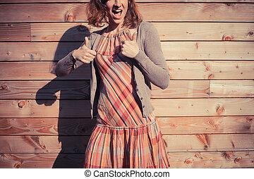mulher jovem, dar, polegares cima, exterior, madeira, cabana