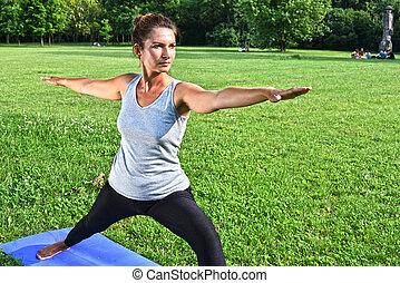 mulher jovem, durante, ioga, meditação, parque