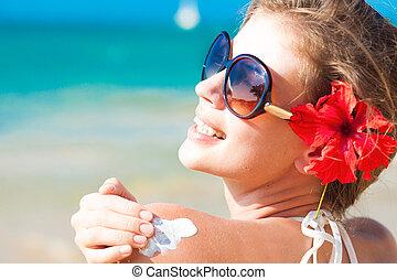 mulher jovem, em, óculos de sol, pôr, creme sol, ligado, ombro
