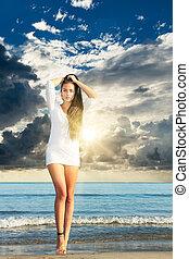 mulher jovem, em, biquíni, praia, em, pôr do sol
