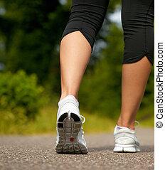 mulher jovem, em, branca, sneakers, andar, ao ar livre