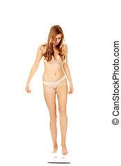 mulher jovem, em, roupa interior, ficar, ligado, escalas