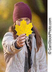 mulher jovem, em, tricotado, chapéu, com, folha amarela