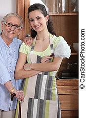 mulher jovem, em, um, avental, com, um, idoso, senhora