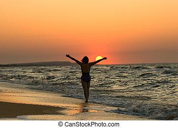 mulher jovem, em, um, pôr do sol