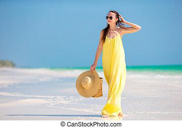 mulher jovem, em, vestido amarelo, com, chapéu, durante, praia tropical, férias
