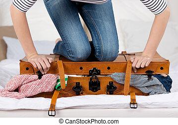 mulher jovem, embalagem, mala, cama