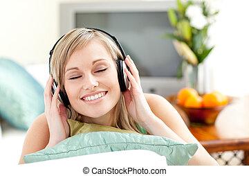 mulher, jovem, encantado, escutar, música, sofá, mentindo