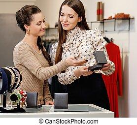 mulher jovem, escolher, jóia, com, assistente loja, ajuda