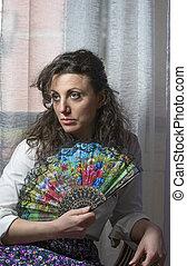 mulher jovem, escondendo, dela, rosto, atrás de, um, ventilador, colorido