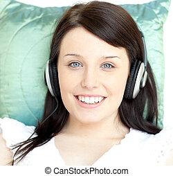 mulher jovem, escutar, música, mentindo, ligado, um, sofá