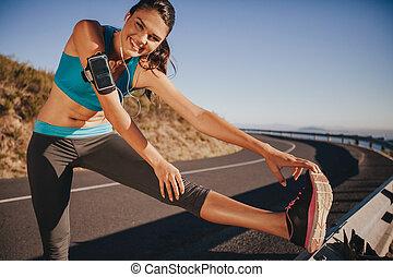 mulher jovem, esticar, ligado, guardrail, ao ar livre