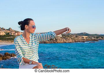 mulher jovem, falando telefone, durante, praia tropical, férias