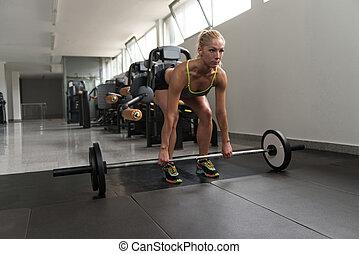 mulher jovem, fazendo, costas, exercício, com, barbell