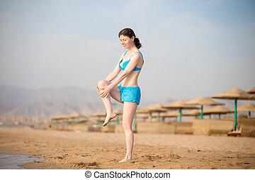 mulher jovem, fazendo, esticar, exercícios, praia