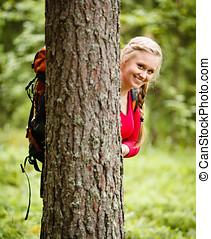mulher jovem, hiker, atrás de, um, árvore