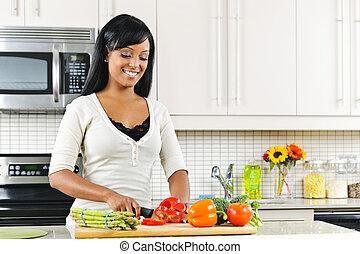 mulher jovem, legumes cortantes, em, cozinha