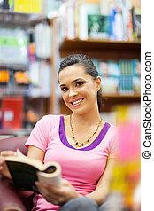 mulher jovem, lendo um livro, em, biblioteca