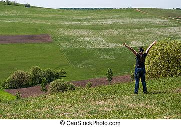 mulher jovem, ligado, um, prado, com, braços levantaram, desfrutando, verão, sol, e, a, ar fresco, desfrutando, a, natureza