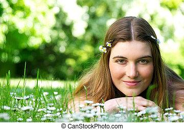 mulher jovem, mentindo, em, prado, com, flores