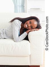 mulher jovem, mentindo, sofá