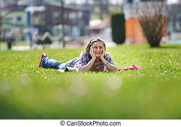 mulher jovem, mentir grama, em, a, summer., relaxante, ao ar livre, olhar, feliz, e, sorrir., natural, felicidade, divertimento, e, harmonia