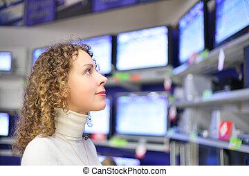 mulher jovem, olha, televisões, em, loja