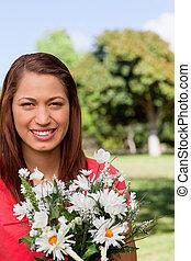 mulher jovem, olhar distância, enquanto, flores, em, um, parque