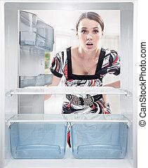 mulher jovem, olhar, vazio, prateleira, em, fridge.