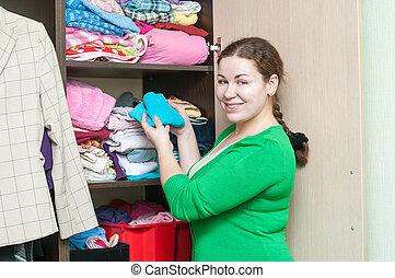 mulher jovem, organizar, roupas, em, a, guarda-roupa, armário, casa