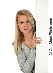 mulher jovem, peeking, detrás, um, parede