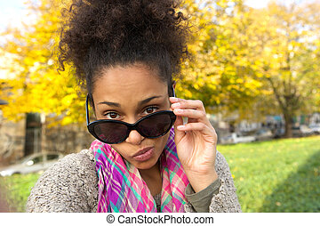 mulher jovem, peeking, sobre, óculos de sol