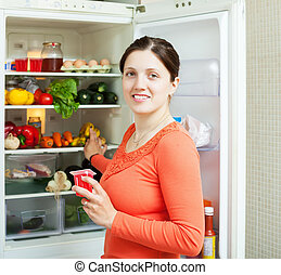 mulher jovem, perto, refrigerador