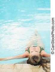 mulher jovem, relaxante, em, piscina, ., vista traseira