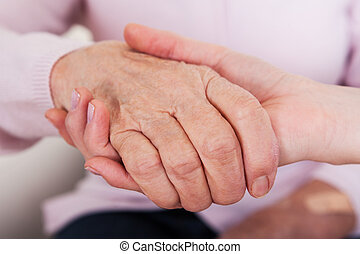 mulher jovem, segurando, sênior, mão mulher