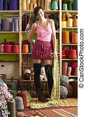 mulher jovem, segurando, tricotado, echarpe, ficar, frente, fio, exposição