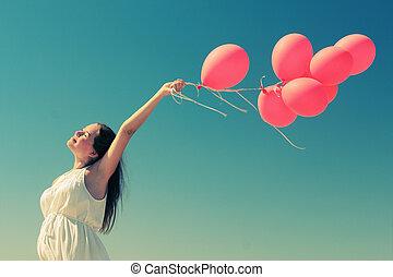 mulher jovem, segurando, vermelho, balões