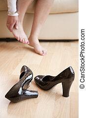 mulher jovem, sentado, casa, rubbing, dela, pés, após, indo, dela, calcanhares altos