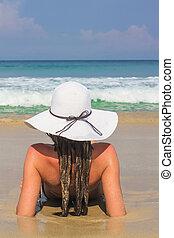 mulher jovem, sentando, em, chapéu branco, desfrutando, férias verão