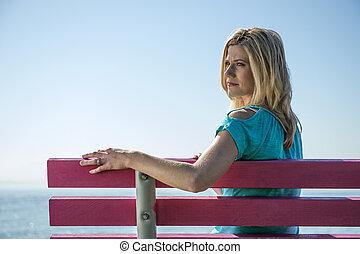 mulher jovem, sentando, ligado, um, banco, em, a, lado mar