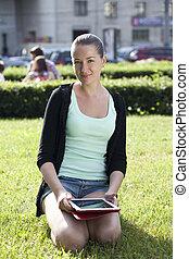 mulher, jovem, sentando, retrato, gramado verde