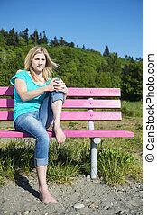 mulher jovem, sentar-se banco, em, praia