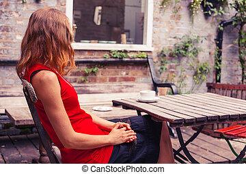 mulher jovem, sentar-se tabela, em, jardim