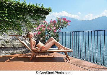 mulher jovem, sunbathing, em, a, como, lago