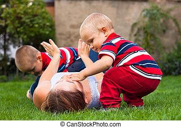 mulher jovem, tocando, com, crianças, ao ar livre