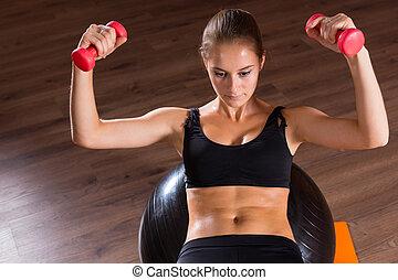 mulher jovem, treinamento, com, dumbbells